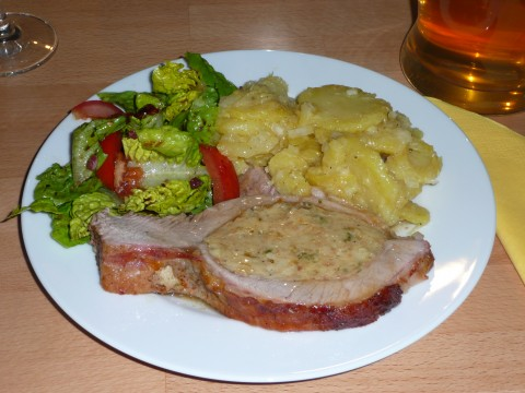 Stuffed veal breast, served with potato salad and green salad